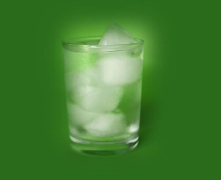 הסמקה פתאומית- טיפ שתיית תמונה של כוס עם מים וקרח מים קרים להסמקה פתאומית. תמונה של כוס מים קרים עם קרח ורקע ירוק.