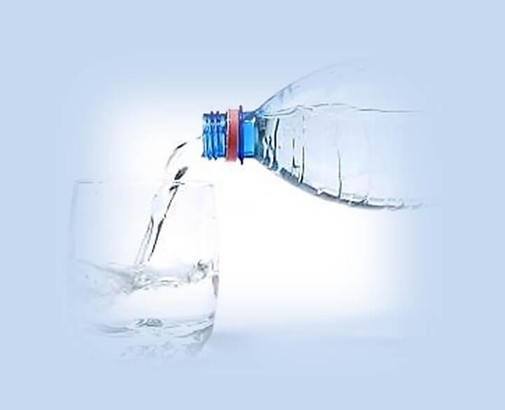 טיפ לריח רע מהפה להרבות בשתיית מים. תמונה של מזיגת מים מבקבוק לכוס מים.