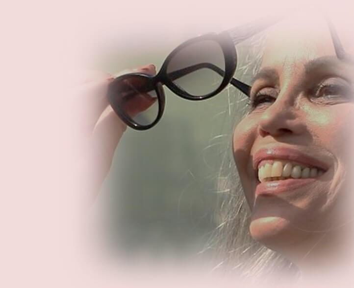 """טיפ לקיץ """"לעולם אינך לבושה בטרם לבשת חיוך"""". תמונת פנים של חלי בן דויד מחייכת עם משקפי שמש ביד."""