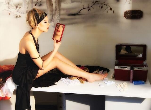 טיפוח בריאות ואנטי אייג'ינג כדרך חיים. תמונה של אישה מטופחת עם מראה ביד.